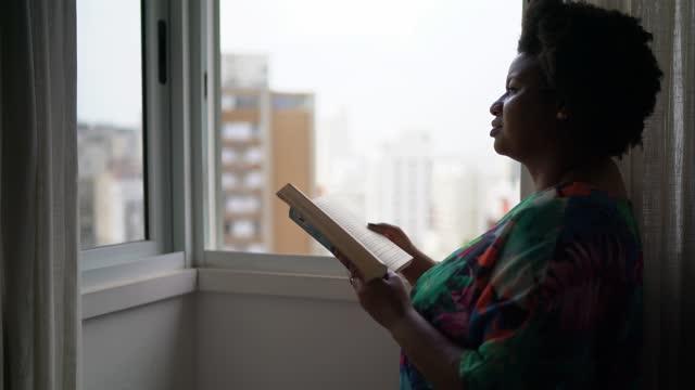 vídeos de stock, filmes e b-roll de mulher lendo livro e olhando pela janela em casa - plena consciência