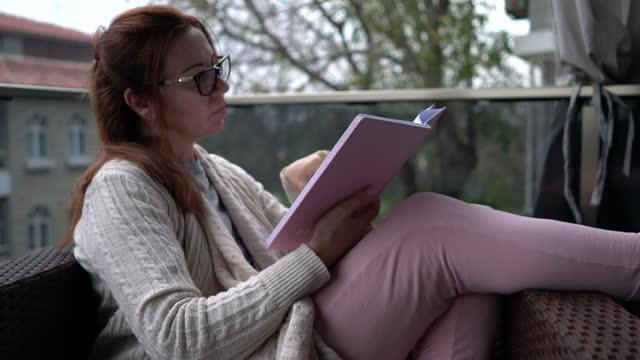 vídeos de stock e filmes b-roll de woman reading book at balcony in winter. - 40 44 anos