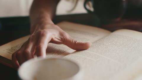 vídeos y material grabado en eventos de stock de mujer leyendo libro en la mesa en el café - hoja