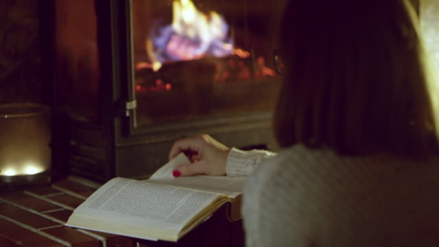 4K Woman reading book by cozy fireplace, real time