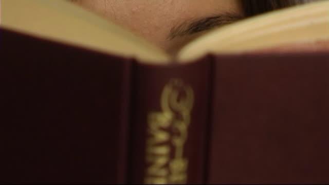 vídeos de stock, filmes e b-roll de woman reading book, close-up of face - equipamento doméstico