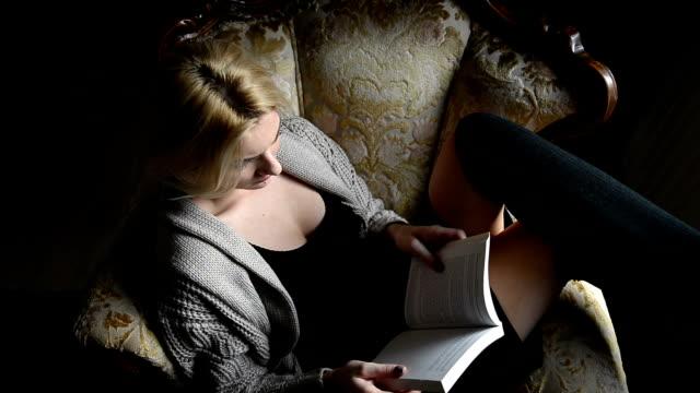 donna lettura libro in poltrona - gambe accavallate video stock e b–roll