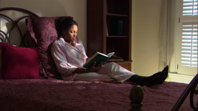 vídeos de stock e filmes b-roll de woman reading book in bed - só mulheres de idade mediana