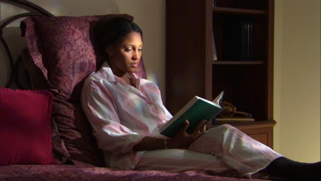 woman reading book in bed - andere clips dieser aufnahmen anzeigen 1282 stock-videos und b-roll-filmmaterial