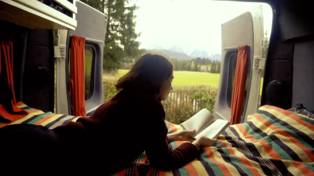 vídeos de stock e filmes b-roll de woman reading book  in camper van with view on alps - acampar