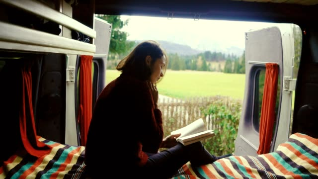 woman reading book  in camper van with view on alps - furgone video stock e b–roll