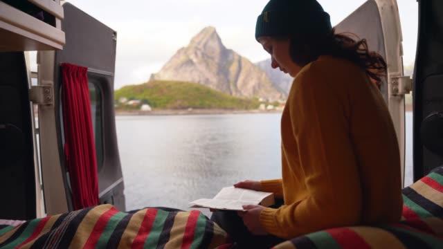 libro di lettura donna in camper con vista sul mare sull'isola delle lofoten - furgone video stock e b–roll