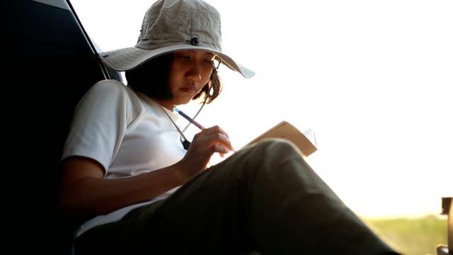 vidéos et rushes de livre de lecture de femme dans la voiture avec la montagne de vue. - carnet