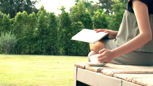 vídeos de stock e filmes b-roll de woman reading book in garden - óculos de leitura