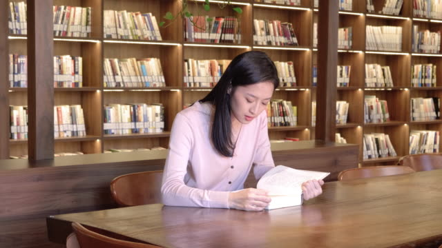 ds ms woman reading book in library and waving at camera, beijing, china - library stock videos & royalty-free footage