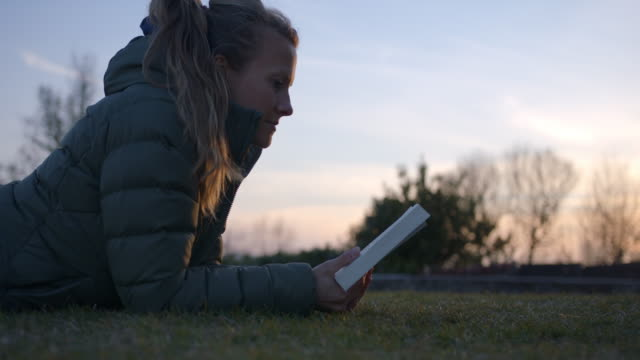 woman reading book in park at sunset, laying on grass - one mid adult woman only stock videos & royalty-free footage