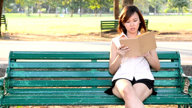 woman reading book in the beautiful park - one young woman only stock videos & royalty-free footage