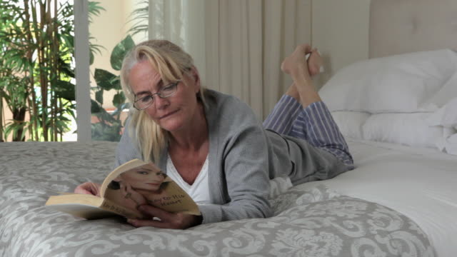 woman reading book on bed - double bed stock videos & royalty-free footage