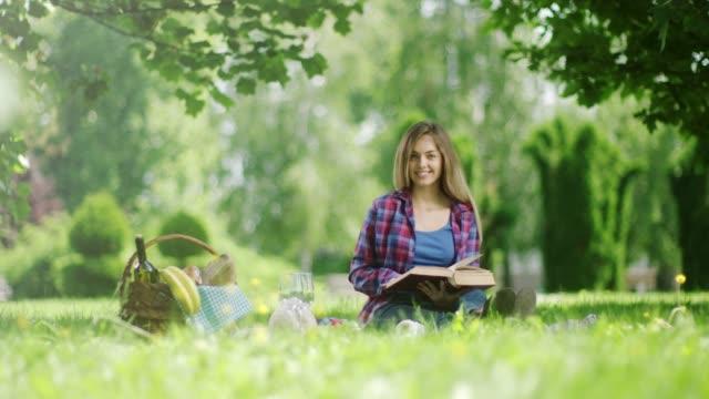 自然の中でピクニックに本を読む女性 - ギフトバスケット点の映像素材/bロール