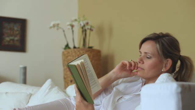 vídeos de stock e filmes b-roll de ms woman reading book on sofa / potsdam, brandenburg, germany - 40 44 anos