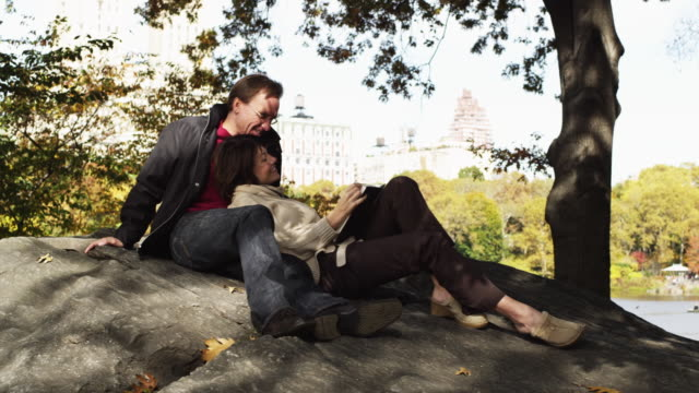 ws pan woman reading book resting on man's lap in central park / new york city, new york state, usa - riposarsi video stock e b–roll