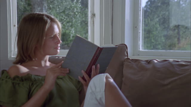 MS Woman reading book sitting on sofa by window, Ryd, Smaland, Sweden