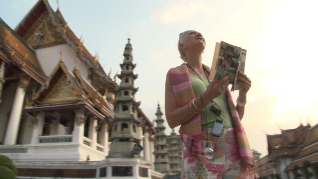 MS LA DS Woman reading guidebook at Wat Phra Kaew (Temple of the Emerald Buddha), Bangkok, Thailand