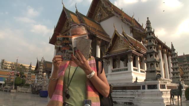CU TU Woman reading guidebook at Wat Phra Kaew (Temple of the Emerald Buddha), Bangkok, Thailand