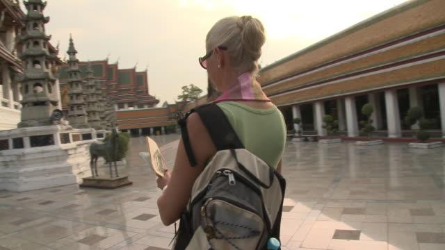 MS DS Woman reading guidebook at Wat Phra Kaew (Temple of the Emerald Buddha), Bangkok, Thailand