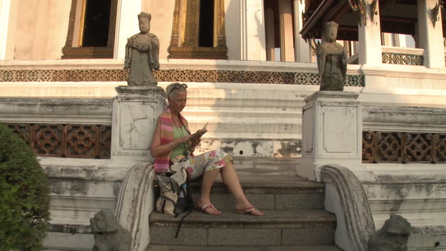 WS ZI MS Woman reading guidebook on temple steps, Wat Phra Kaew (Temple of the Emerald Buddha), Bangkok, Thailand