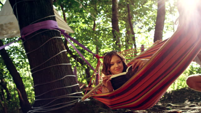 woman reading in a hammock. outdoor relaxation - hammock stock videos & royalty-free footage