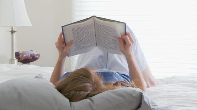 vídeos y material grabado en eventos de stock de woman reading in bed - encuadre de tres cuartos