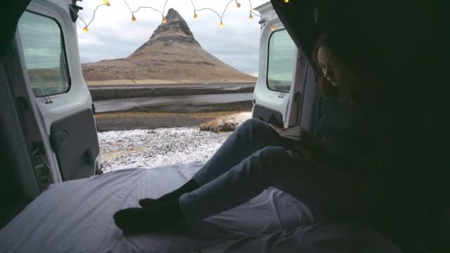 Woman reading in camper van near Kirkjufell mountain in Iceland in winter