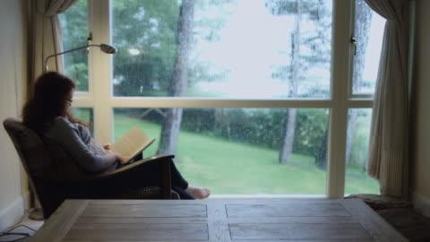 stockvideo's en b-roll-footage met vrouw lezing in gezellige kamer - comfortabel