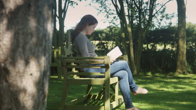 woman reading in garden - dappled light stock videos and b-roll footage