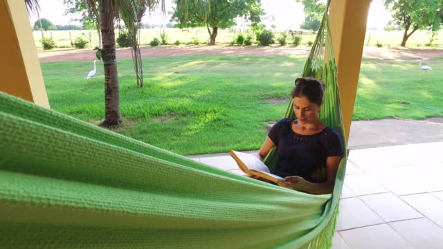 vídeos de stock, filmes e b-roll de woman reading in hammock in tropical setting - rede de dormir