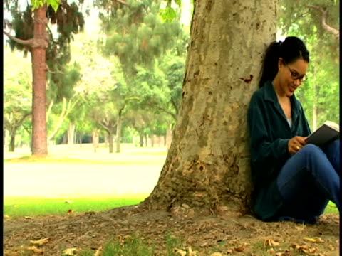 woman reading in the park - 後ろで束ねた髪点の映像素材/bロール
