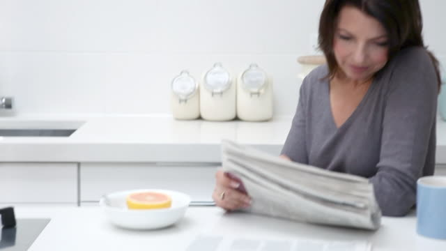 Woman reading newspaper at breakfast