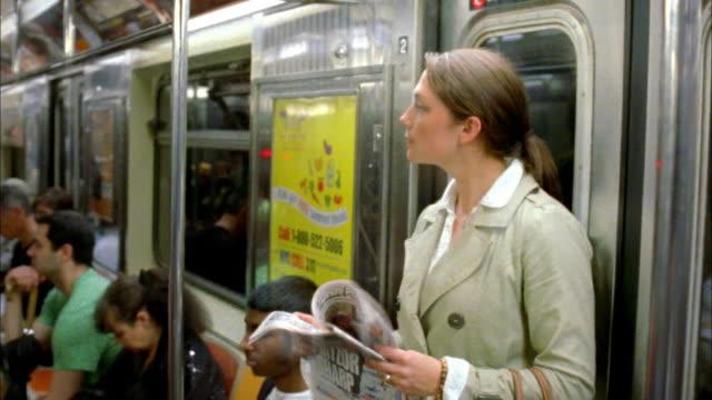 ms woman reading newspaper on subway train, new york city, new york, usa - 乗り物内部点の映像素材/bロール