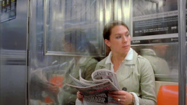 MS Woman reading newspaper on subway train, New York City, New York, USA
