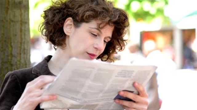 DOLLY:  Donna lettura giornale all'aperto