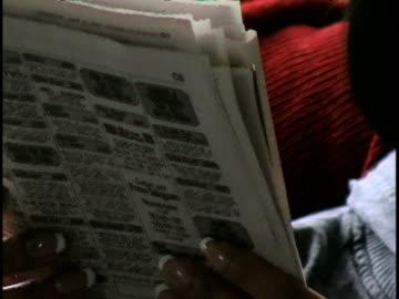 stockvideo's en b-roll-footage met woman reading newspaper - krant