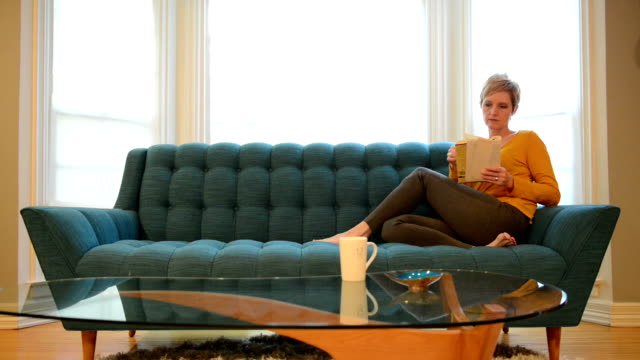 vídeos y material grabado en eventos de stock de mujer leyendo en un sofá cama - mesa baja de salón