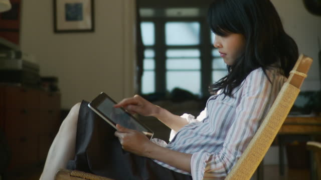 MS Woman reading on digital tablet at home / Brooklyn, New York, USA