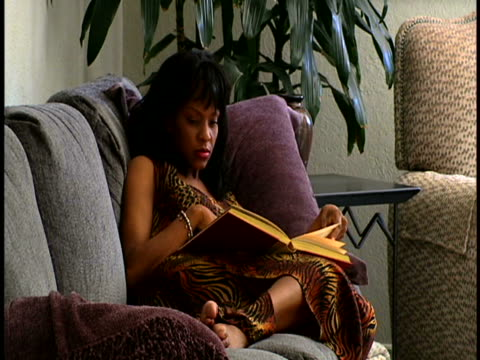 vídeos y material grabado en eventos de stock de woman reading on sofa - recostarse