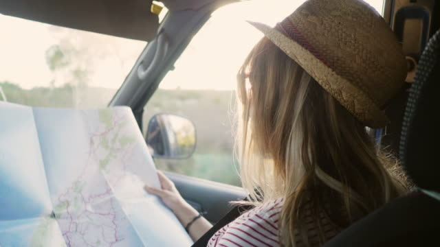 woman reading road map while sitting in car - road trip stock videos & royalty-free footage