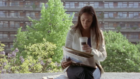 woman reading travel section of newspaper and drinking coffee on balcony of high rise / london, england - balcony stock videos & royalty-free footage