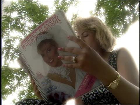 vídeos de stock, filmes e b-roll de woman reading wedding planner in pennsylvania - revista publicação