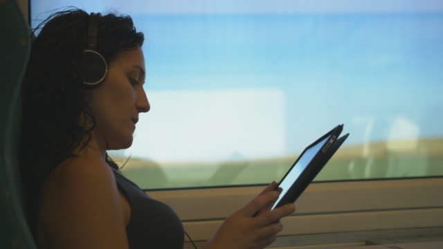 Woman reading with a tablet while travelling