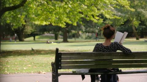 woman reads book on park bench - lesen stock-videos und b-roll-filmmaterial