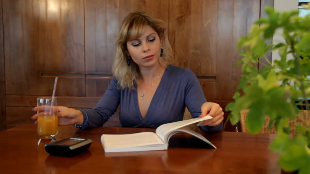 Woman reads book while waiting for someone