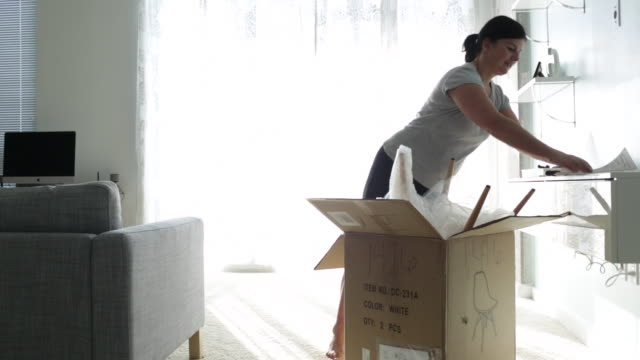Woman reads instructions for assembling furniture, she removes chair from box and looks at it with happinesss.