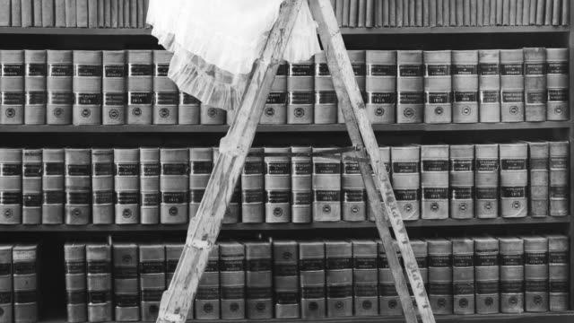 vidéos et rushes de a woman reads on a ladder near bookshelves in a library. - historique