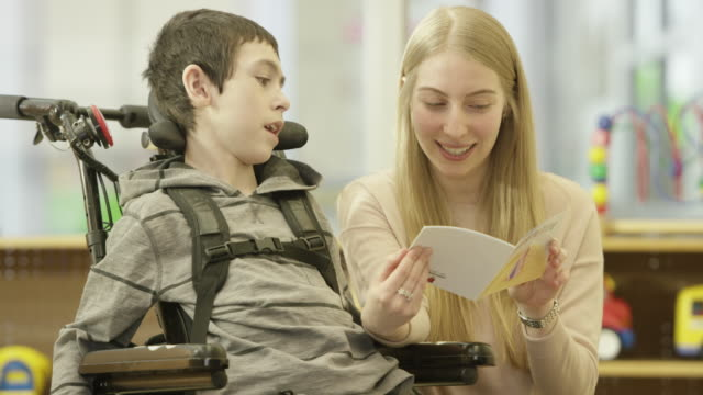 woman reads to child with physical disability - disability stock videos & royalty-free footage