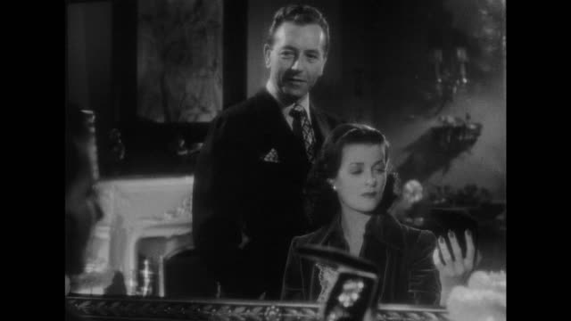 1948 Woman (Joan Bennett) realizes man (Paul Henreid) is saying goodbye with a jewelery gift